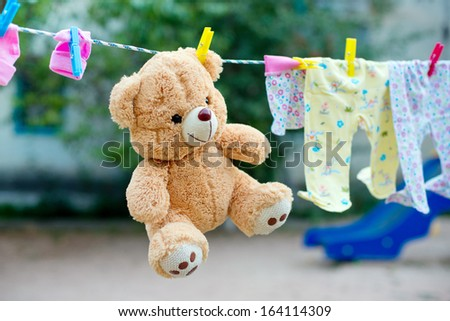 baby clothes and accessories hanging on clothesline outdoors - stock photo