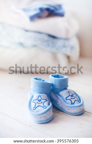 Baby clothes.baby shoes for boy on a blue background - stock photo