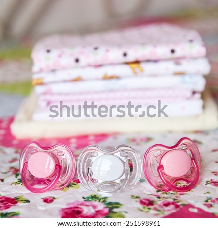 baby clothes, diapers and pacifiers beautiful fabric for girls - stock photo