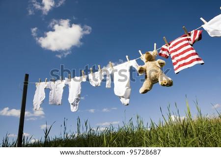 Baby Clothing and a teddybear on a clothesline towards blue sky - stock photo