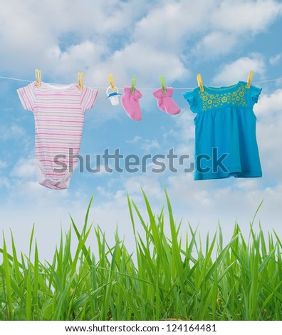 Baby Clothing on a clothesline towards blue sky - stock photo