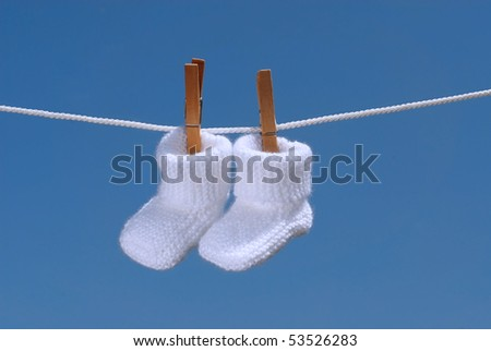 baby concept: white baby booties hanging on a clothes line - stock photo