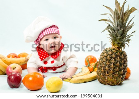 Baby cook girl wearing chef hat with fresh fruits. Use it for a child, healthy food concept - stock photo