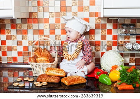 Baby cook with bread  sits on a kitchen table - stock photo