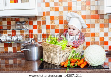 Baby cook with vegetables sits in a wattled basket on a kitchen table - stock photo