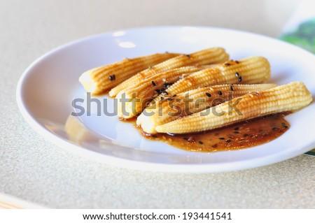 baby corn Salad wite sesame sauce on white dish - stock photo