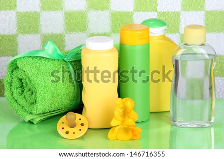 Baby cosmetics and towel in bathroom on green tile wall background - stock photo
