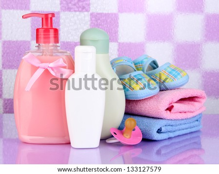 Baby cosmetics and towels  in bathroom on violet tile wall background - stock photo