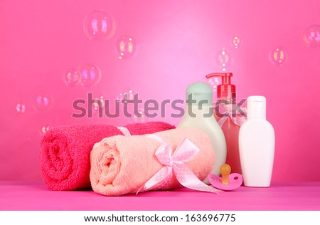 Baby cosmetics and towels on pink background - stock photo
