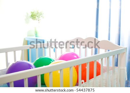 baby cot with colorful balls as concept of great occasion of birth - stock photo