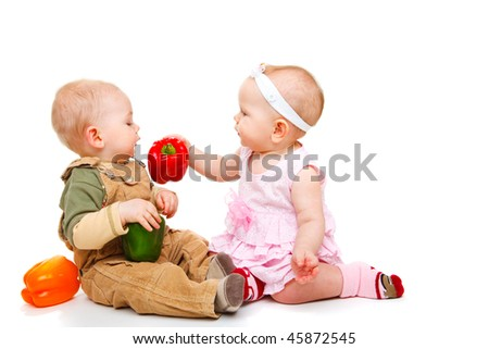 Baby couple eating peppers - stock photo
