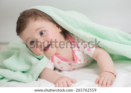baby covered with a bath towel lying on tummy in the bathroom. Close portrait