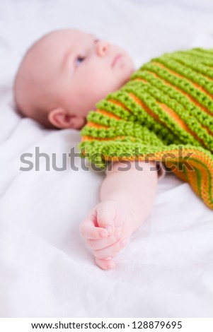 baby covered with green knitted blanket laying on white sheets in bed - selective focus on fingers - stock photo