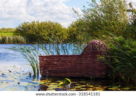 baby cradle made from willow branches in the reed of a river - stock photo