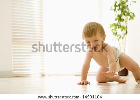 Baby crawling indoors smiling - stock photo