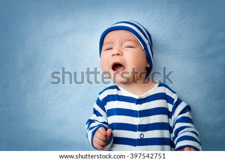 Baby crying in bed - stock photo