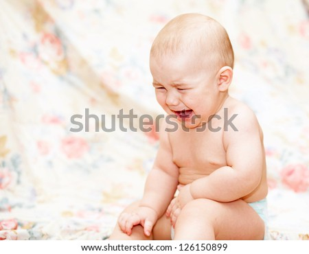 Baby crying sitting  on the floor - stock photo