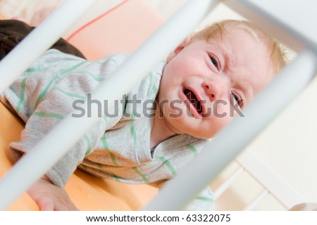 baby crys in the latticed bedsted through bars - stock photo