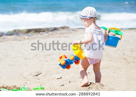 Baby cute and little playing on the beach - stock photo