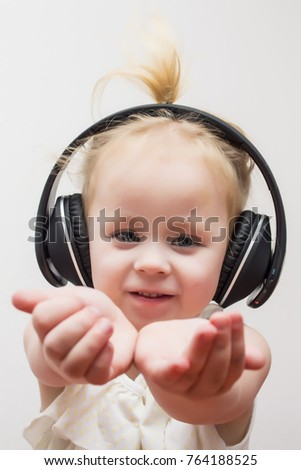baby, cute girl in wireless headphones listening to music