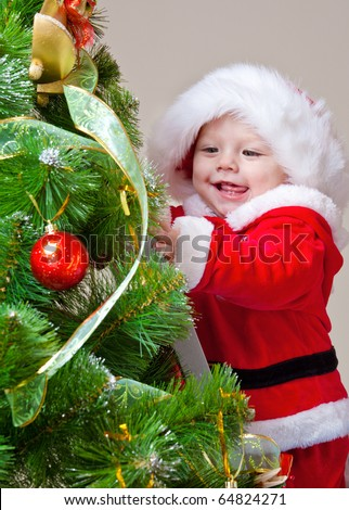 Baby decorating Christmas tree, over gray - stock photo