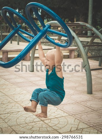 Baby doing exercises on a playground. Toned - stock photo