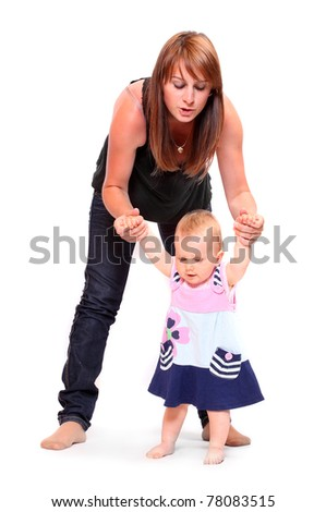 Baby doing her first steps with mother help. Studio shot on white background. - stock photo