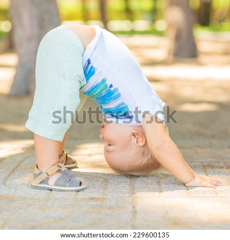 Baby doing yoga exercises. Downward Facing Dog pose. Adho Mukha Svanasana - stock photo