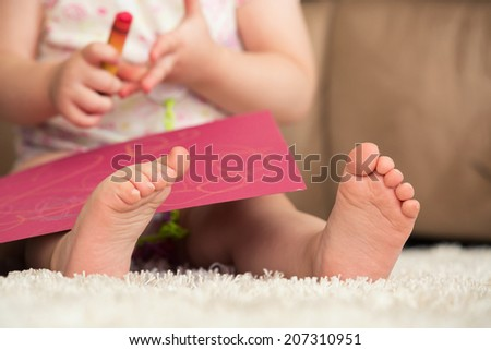 Baby Drawing With Focus on Baby�¢??s feet - stock photo