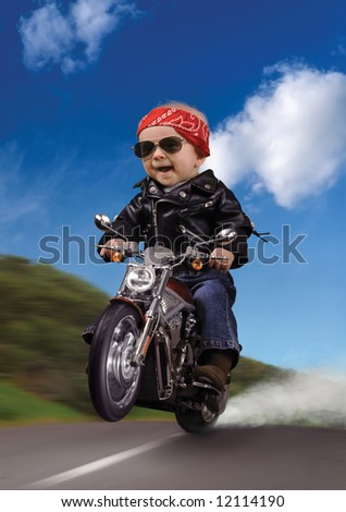 Baby dressed as a biker, popping a wheelie on a motorcycle - stock photo