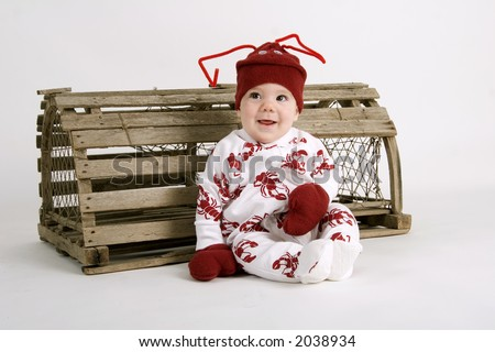Baby dressed in lobster costume sitting next to a lobster trap - stock photo
