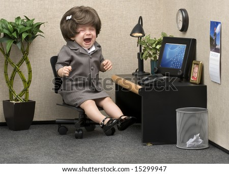 Baby dressed in professional office attire crying at her desk - stock photo