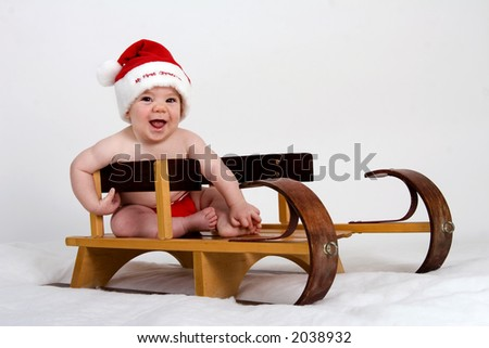 Baby dressed in Santa hat and red diaper sitting in a sled - stock photo