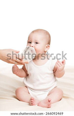 baby drinking milk from bottle. Baby holding bottle himself. sweet funny baby drinking. Pretty baby girl drinking milk from bottle - stock photo