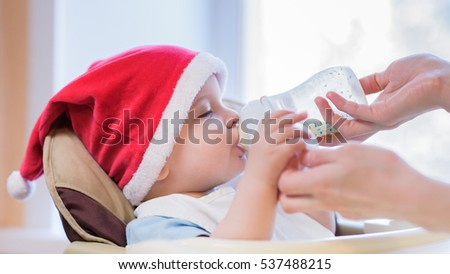baby drinking milk in Christmas red hat