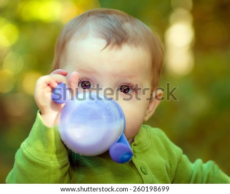 Baby drinking milk out of a sippy cup - stock photo