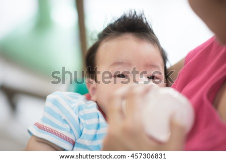 Baby drinking mother breast feeding milk from bottle mother holding