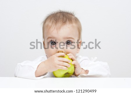 baby eating apple, looking at camera