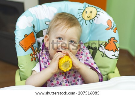 baby eating corn - stock photo