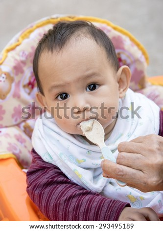Baby eating food by mother feeding - stock photo