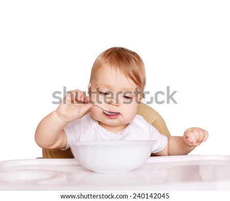 Baby eating healthy food. Isolated on white background.