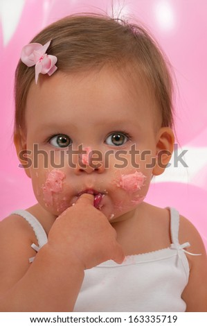Baby eating her birthday cupcake - stock photo
