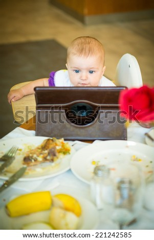 baby eats at the table and looking cartoons on the tablet  - stock photo