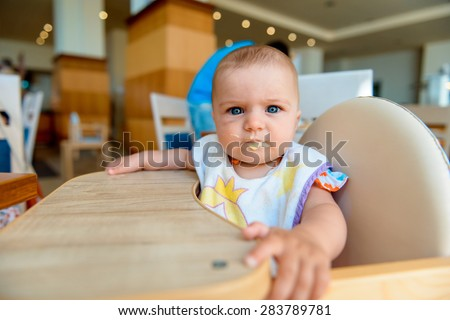 baby eats at the table. child eats baby cereal. Little girl eating baby mashed.  - stock photo