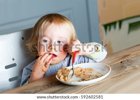 Baby eats porridge spoon mashed