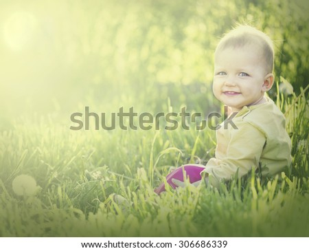 Baby eleven months months sitting in the grass - stock photo