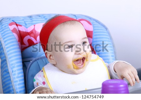 Baby enjoy her first lunch - stock photo