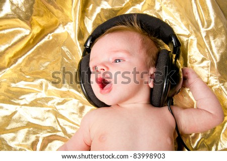 Baby enjoying listening to sound from headphones - stock photo