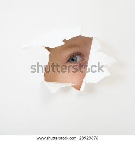 Baby eye peep through hole in sheet of paper. Concept of childish curiosity - stock photo