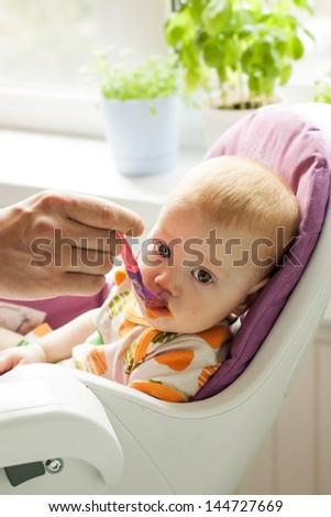 Baby feeding by his mother from spoon - stock photo